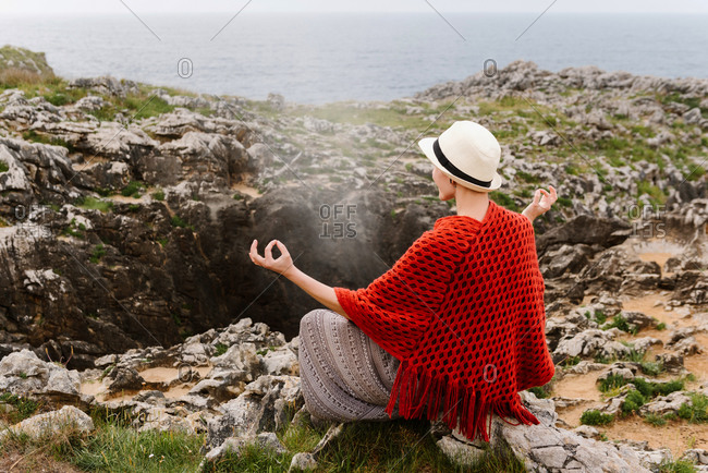 Back view of unrecognizable female traveler in stylish knitwear and hat meditating with mudra gesture while sitting on stone in front of Jesters of Arenillas geyser during trip to Asturian coast of Spain