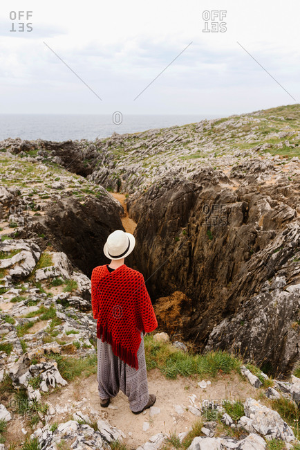 High angle back view of unrecognizable female traveler in stylish outfit and hat standing on edge of rocky cleft on seashore while exploring Asturian coast of Spain during summer vacation
