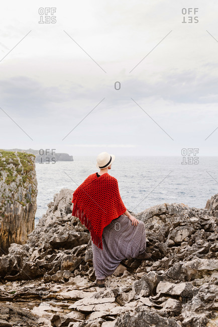 Full length back view of unrecognizable woman in stylish clothes standing on edge of rocky cliff against cloudy sky and admiring seascape while enjoying holidays on Asturian coast of Spain