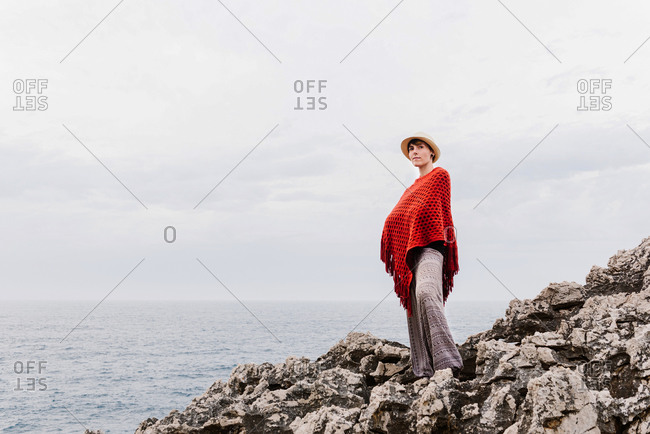 From below full length of woman in stylish clothes standing on edge of rocky cliff against cloudy sky and admiring seascape while enjoying holidays on Asturian coast of Spain