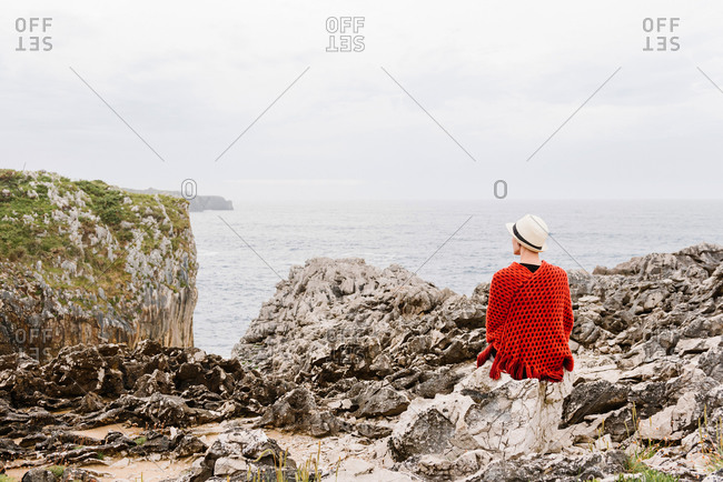 Back view of unrecognizable woman in stylish clothes sitting on edge of rocky cliff against cloudy sky and admiring seascape while enjoying holidays on Asturian coast of Spain