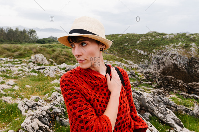 Female traveler in red knitted poncho and hat walking on grassy hill while enjoying holidays in Asturias in Spain