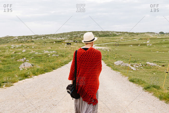 Back view of unrecognizable female traveler in red knitted poncho and hat walking on dirt path leading through grassy hills while enjoying holidays in Asturias in Spain