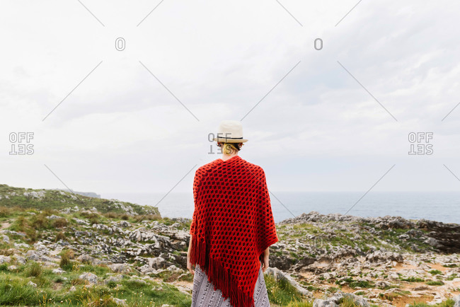 Back view of unrecognizable female traveler in stylish outfit and hat standing on edge of rocky cliff on seashore while exploring Asturian coast of Spain during summer vacation