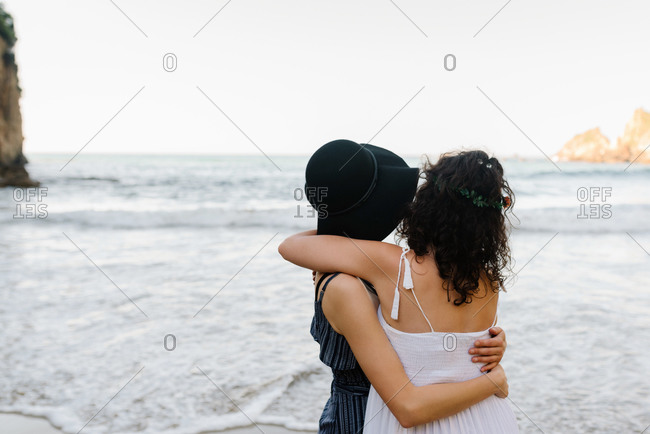 Back view of faceless girlfriends in sundresses cuddling gently each other near wavy sea with ridge under serene sky during vacation