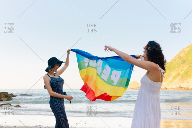Side view of slim lady in hat and cheerful girlfriend in sundress raising colorful pride flag while standing on sandy shore near wavy ocean during vacation and looking at each other