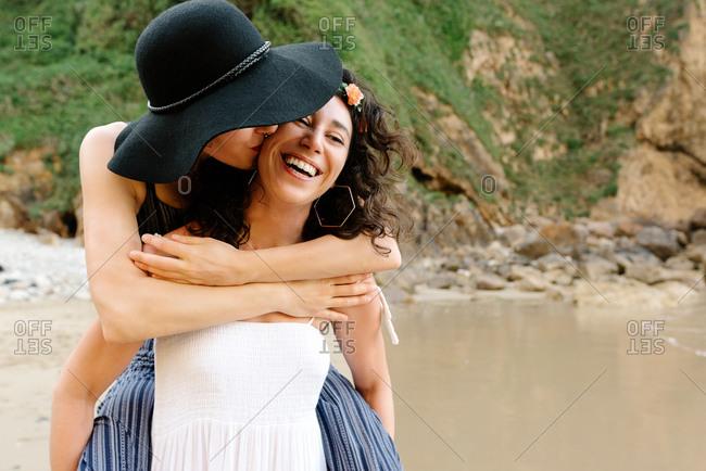 Lesbian couple embracing near ocean during honeymoon in summer