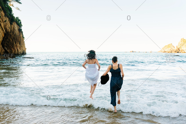 Back view of anonymous barefoot female friends in sundresses running on ocean forming foam near sandy coast and ridge under serene sky during vacation