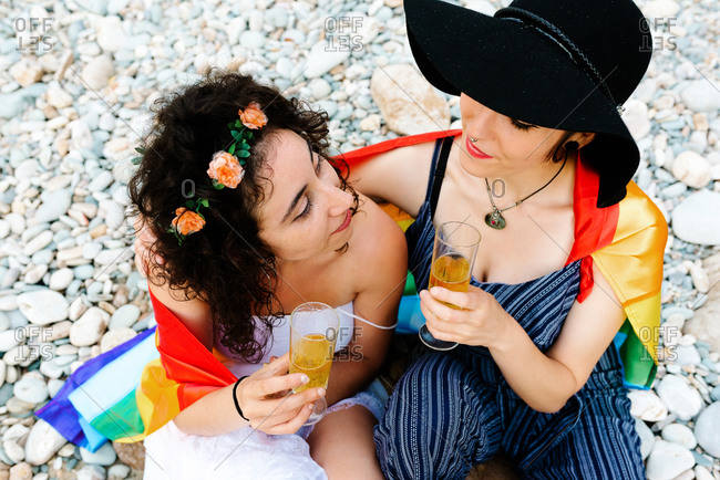 High angle of tender lesbian couple sitting on stony beach and covering with rainbow flag while embracing and clinking glasses with champagne