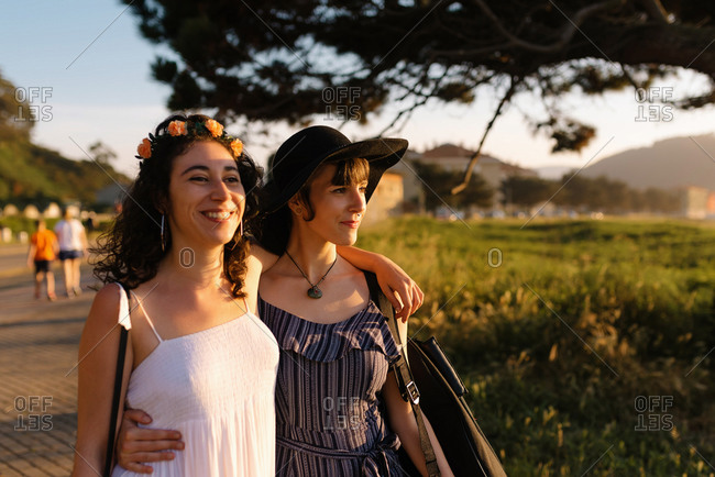 Homosexual couple of women in love hugging and enjoying stroll during sunset in summer