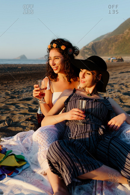 Delighted lesbian couple sitting on sandy beach with glasses of alcohol beverage and admiring sunset during summer vacation