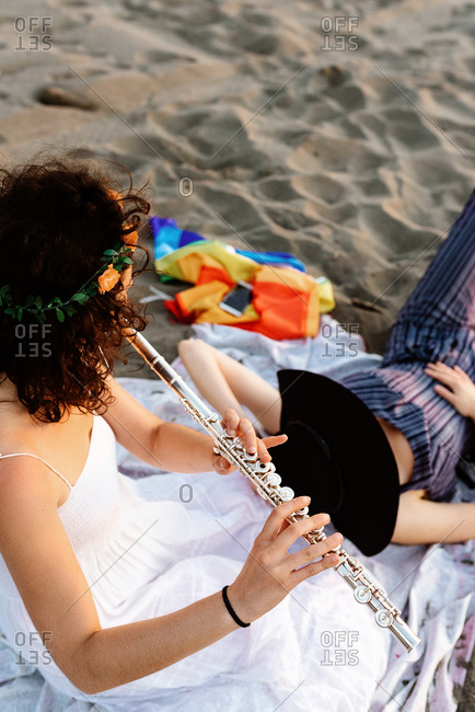 Skilled female musician sitting on blanket on shore and playing flute for girlfriend while resting in evening