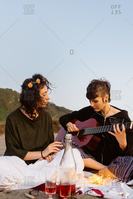 Talented female musician playing acoustic guitar for girlfriend during picnic at seaside at sunset