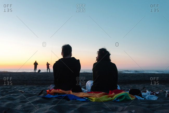 Cheerful girlfriends spending time together on sandy beach in daylight