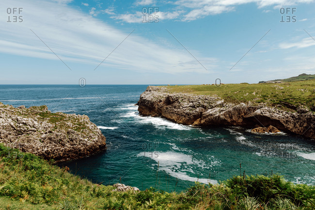 Picturesque view of endless foamy sea near cliffs with uneven surface partially covered with grass under serene sky with clouds