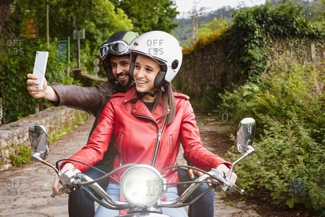 Cheerful man in helmet taking selfie on cellphone while sitting on motorcycle with smiling girlfriend in leather jacket riding on pathway near lush green shrubs on weekend