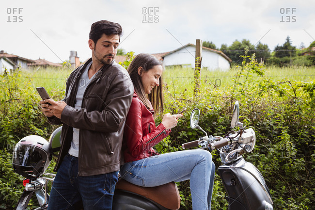 Side view of masculine guy using social media on cellphone while standing near content beloved sitting on motorcycle near lush green shrubs in rural zone under cloudy sky
