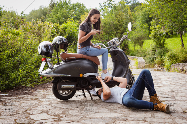 Male in casual wear lying on walkway while fixing motorbike and talking to content girlfriend near lush green bushes in countryside