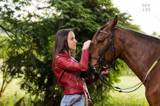 Side view of thoughtful young female in jeans and leather jacket stroking warm blooded stallion with bridle and reins while standing near shrub in rural zone and looking away