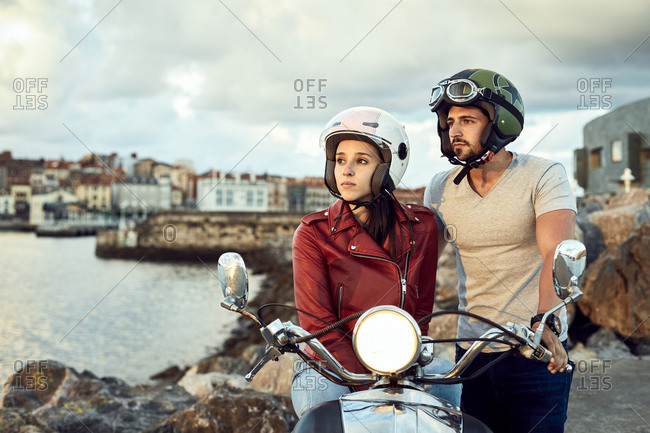 Thoughtful man in helmet standing near wistful girlfriend in leather jacket sitting on motorcycle with headlight on while contemplating picturesque river during vacation and looking away