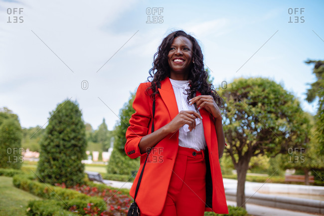 Slim pensive African American female in colorful suit touching hair while looking away in city park near green shrubs in summer under cloudy sky