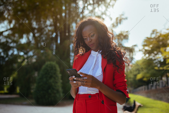 Slim elegant African American female in red clothes and shoulder bag using mobile phone while standing near colorful green trees in park