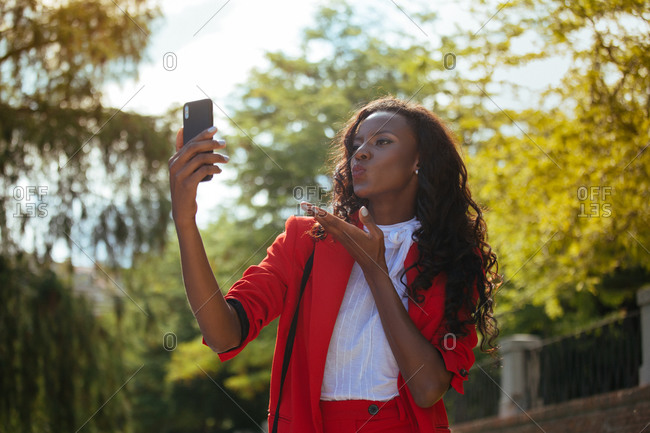 Slim elegant African American female in red clothes and shoulder bag taking selfie on cellphone while standing near colorful green trees in park