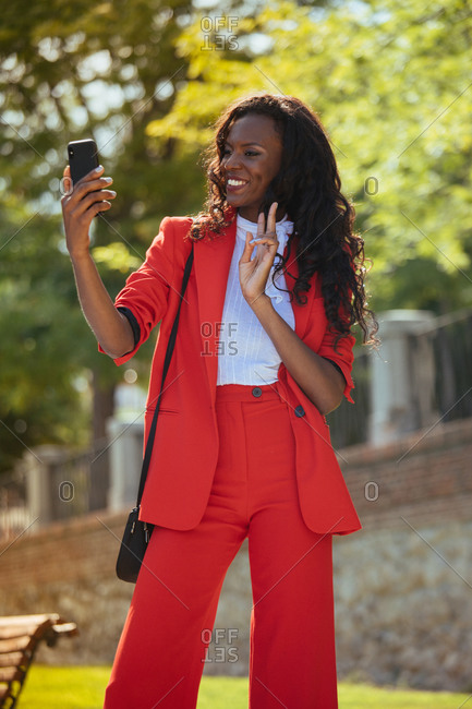 Slim elegant African American female in red clothes and shoulder bag taking selfie on cellphone while standing with pouting lips near colorful green trees in park