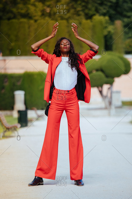 Slim African American woman in bright trousers and jacket standing on walkway leaned on hands near wooden bench and shrubs in city park with eyes closed