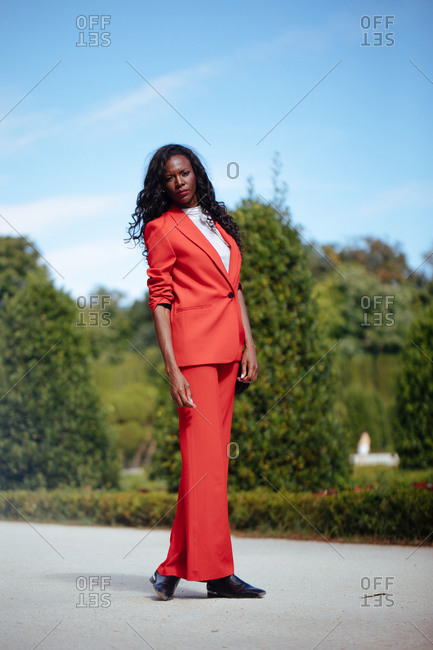 Slim African American woman in bright trousers and jacket standing on walkway leaned on hands near wooden bench and shrubs in city park and looking at camera