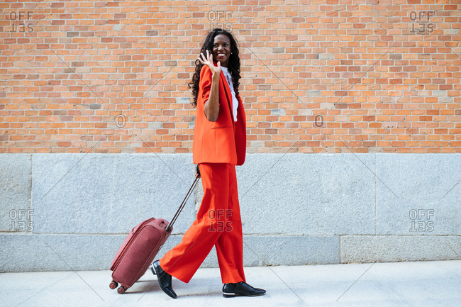 Side view of cheerful slender African American female in red suit saying hello while strolling with suitcase on walkway near building with brick wall in daylight and looking away