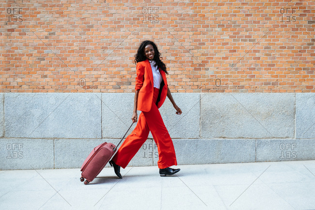 Side view of cheerful slender African American female in red suit strolling with suitcase on walkway near building with brick wall in daylight and looking at camera