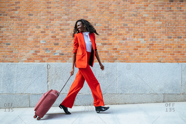 Side view of cheerful slender African American female in red suit strolling with suitcase on walkway near building with brick wall in daylight and looking away