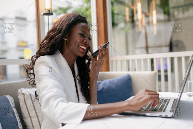 Positive African American busy female entrepreneur wearing white formal clothes sitting on sofa and browsing laptop while chatting via smartphone