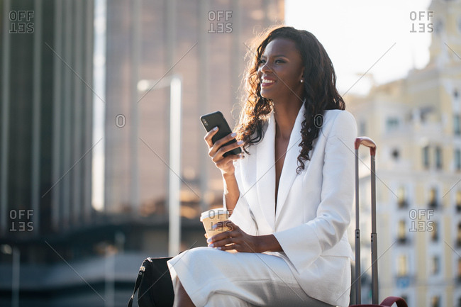 Positive African American businesswoman in elegant white clothes browsing cellphone and having coffee while sitting on street with suitcase
