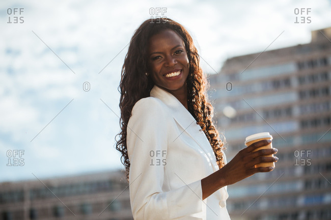 Cheerful black woman holding a cup of hot drink walking along street with modern architecture looking at camera