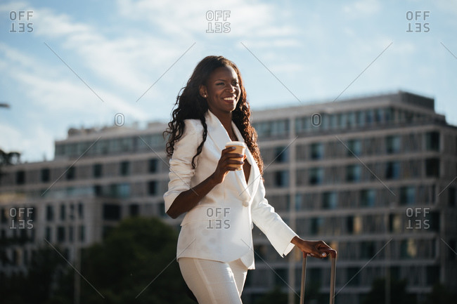 Cheerful black woman with suitcase and cup of hot drink walking along street with modern architecture