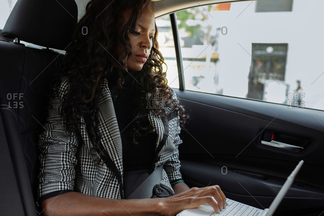 Side view of serious young African American businesswoman working with electronic documents on laptop during trip in car in city