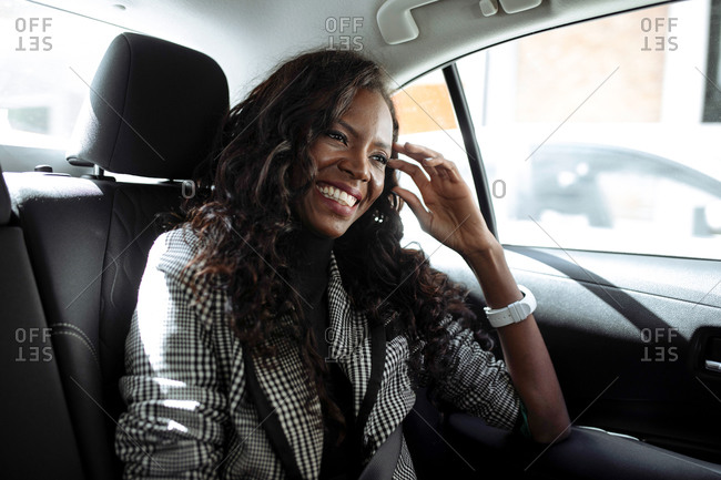 Cheerful African American female entrepreneur in formal clothes during trip in car on city street