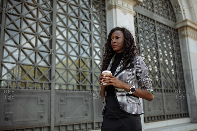 Confident well dressed ethnic businesswoman with cup of takeaway coffee walking near metal door on wall of city building and looking away