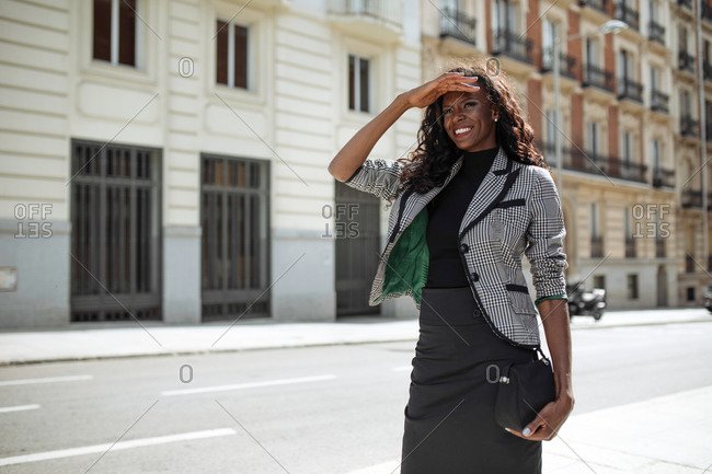 Cheerful young African American businesswoman in elegant formal wear walking on city street looking away