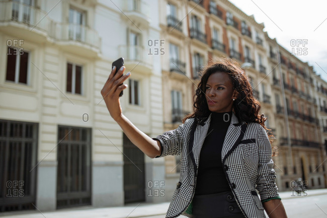 Confident young African American businesswoman in stylish formal outfit standing on city street and taking selfie on smartphone