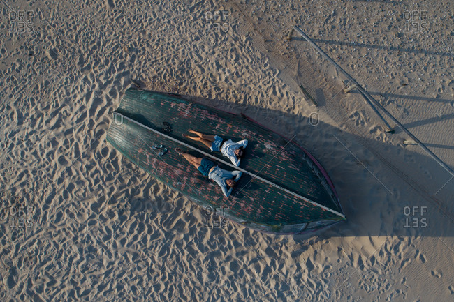 Drone view full body faceless couple in casual summer wear relaxing with head on hands on wooden rowboat turned upside down on sandy beach