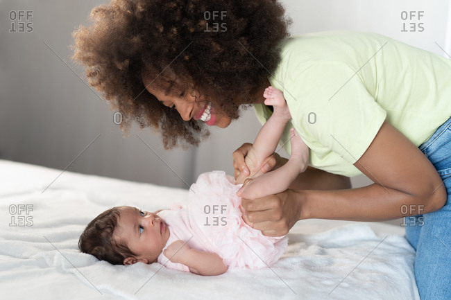Side view of cheerful African American woman having fun with adorable newborn child lying on soft bed