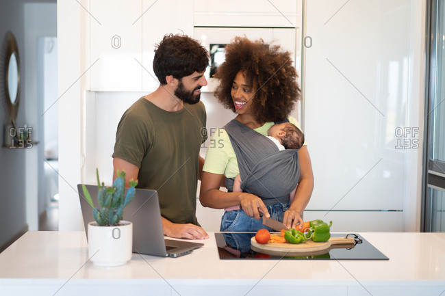 Content black mother with baby in sling cutting vegetables and Arab father working on laptop while standing at counter in kitchen