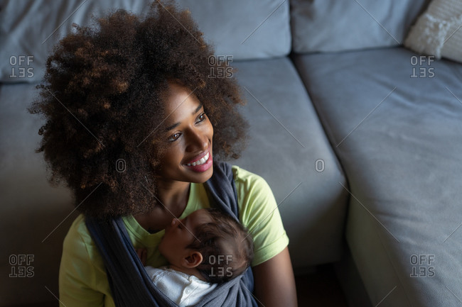 From above gentle African American mother sitting on floor with adorable sleeping baby in sling and looking at camera