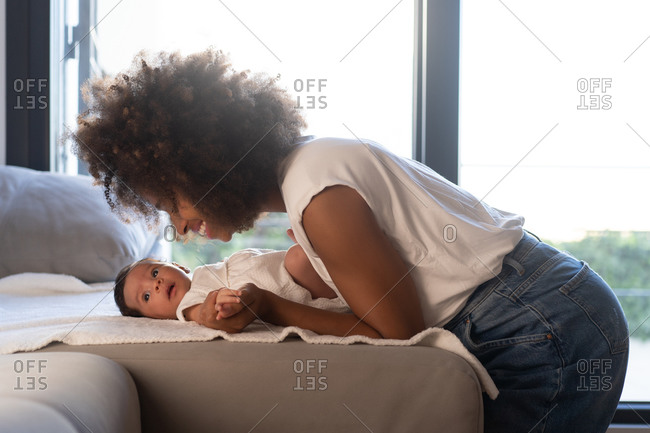 Side view of delighted ethnic African American woman playing with cute baby on sofa at home
