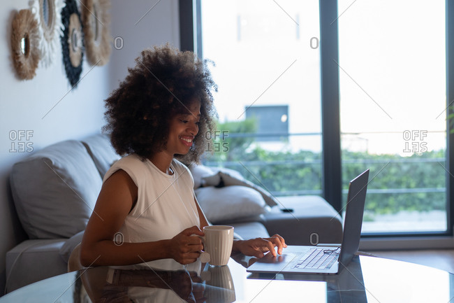 Concentrated African American female entrepreneur sitting at table with cup of tea and working on remote project while using netbook at home