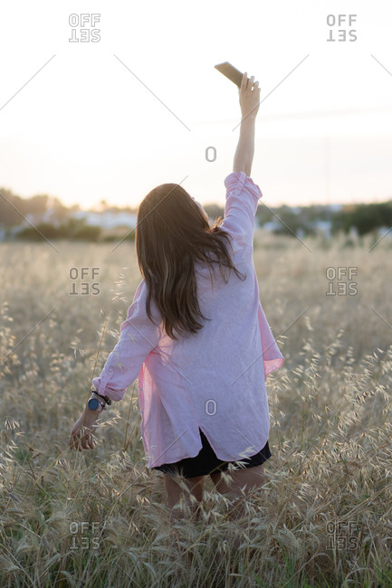 Female standing in dried field and taking photo on smartphone on background of scenic sundown in rural area
