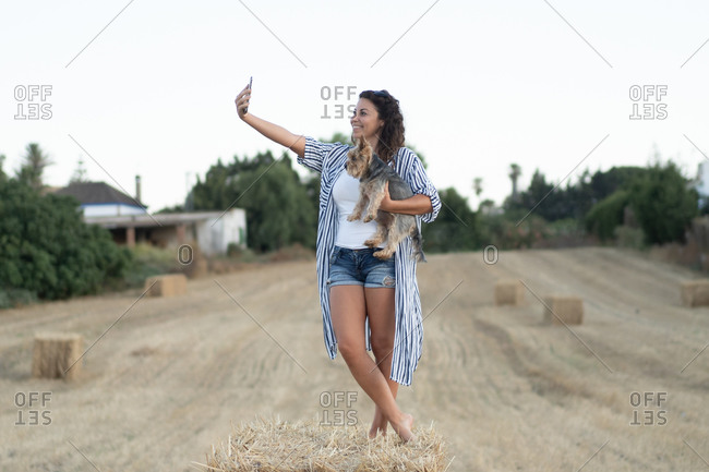 Smiling female standing in dried field with dog and taking photo on smartphone on background of scenic sundown in rural area